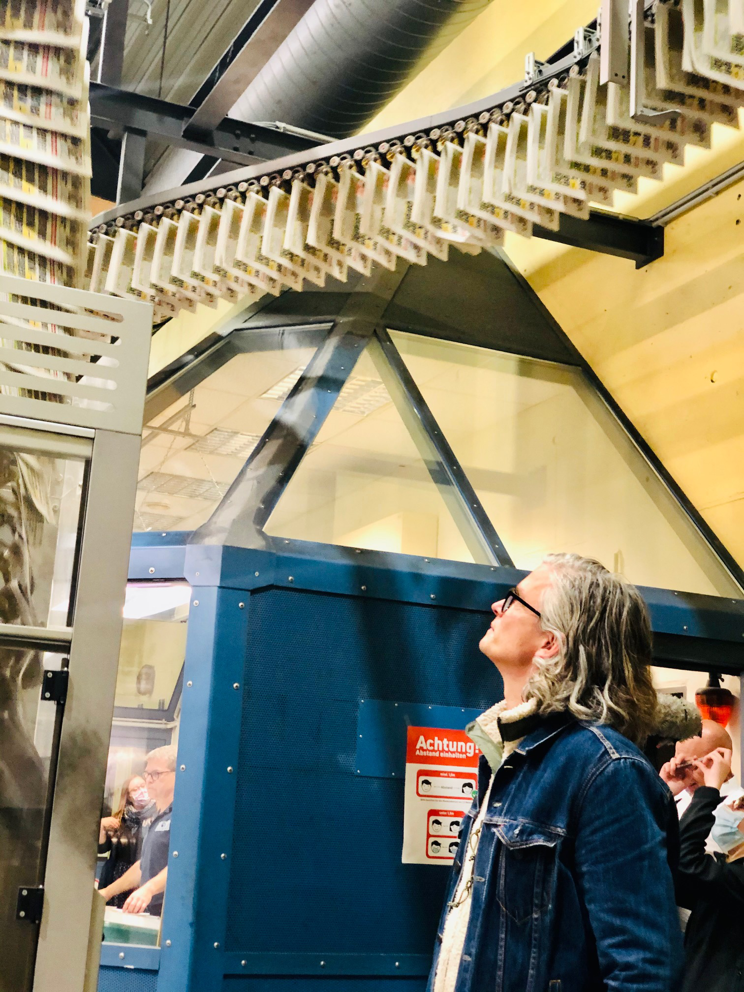Verleger Arist von Harpe vor Zeitungen auf Laufbändern in einer Druckerei
